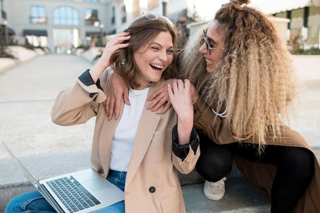 Moças bonitas que riem junto