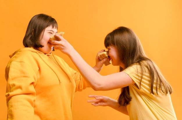 Moças bonitos que jogam com bolo