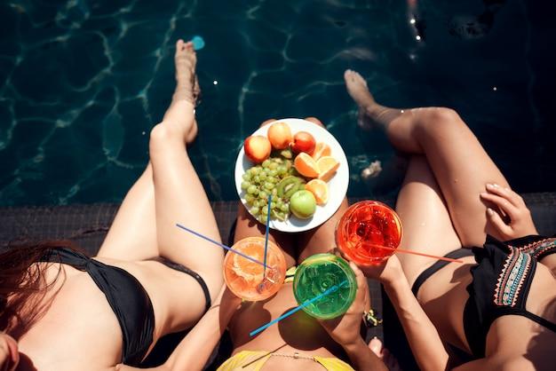 Moças com frutas e coquetéis à beira da piscina
