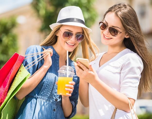 Moças com sacos de compras, olhando para o telefone e sorrindo.