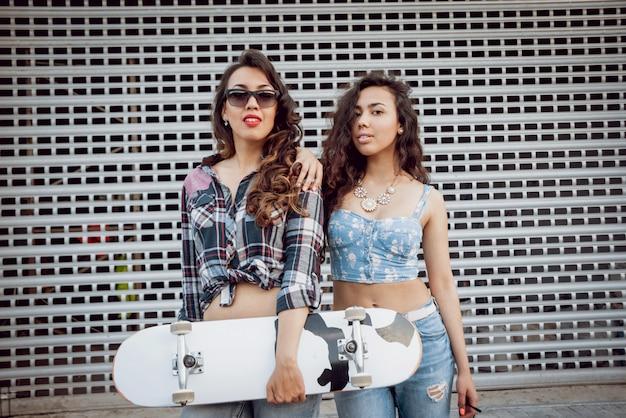 Moças com skate na parede cinza grande.