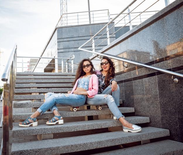 Moças com skate, sentado na escada