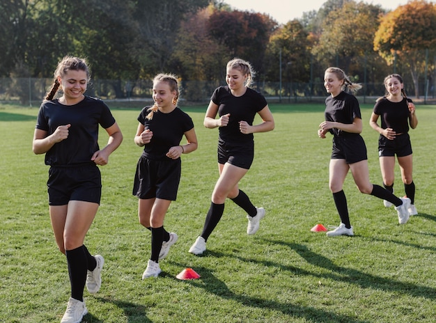 Moças correndo através de cones