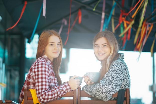 Moças de sorriso que bebem o café