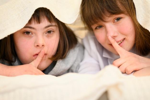 Moças felizes que escondem junto