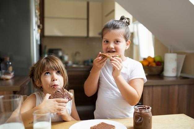 Moças que tomam o café da manhã em casa