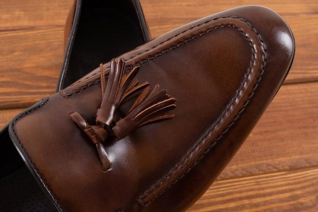 Mocassins clássicos marrons com borlas em suporte de madeira