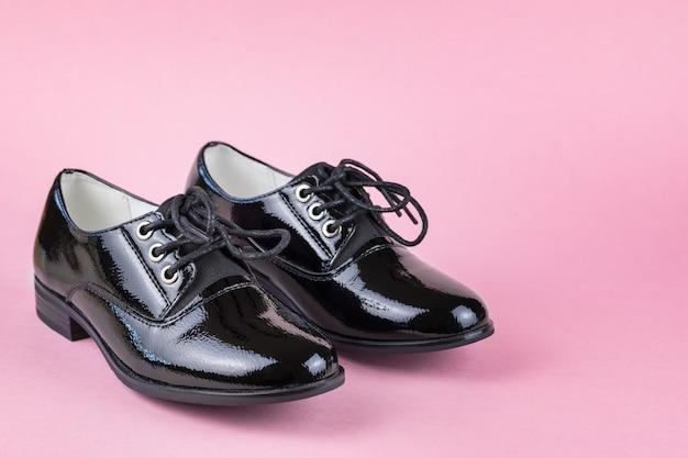 Mocassins de couro femininos elegantes na moda em fundo rosa. sapatos escolares da moda.