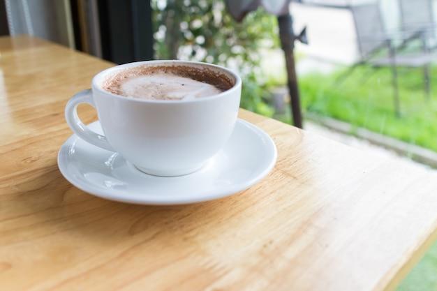 Mocha de café quente com leite de espuma no café rural