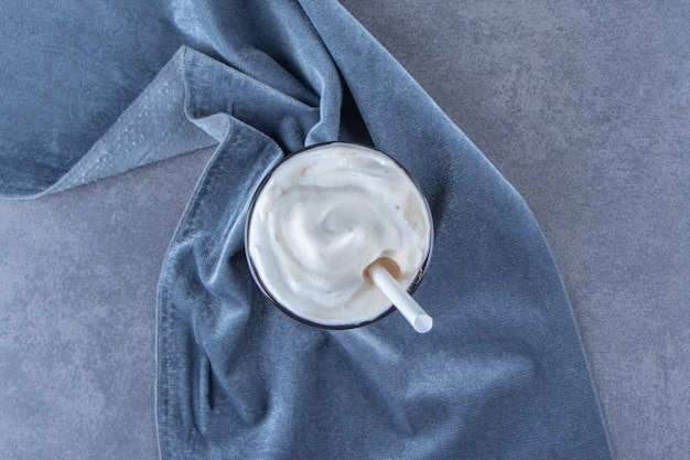 Mocha de chocolate em um copo sobre um pedaço de tecido, na mesa azul.