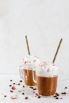Mocha de menta caseiro, bebida de café de natal com bastões de doces, chantilly e calda de menta, na mesa de mármore branco