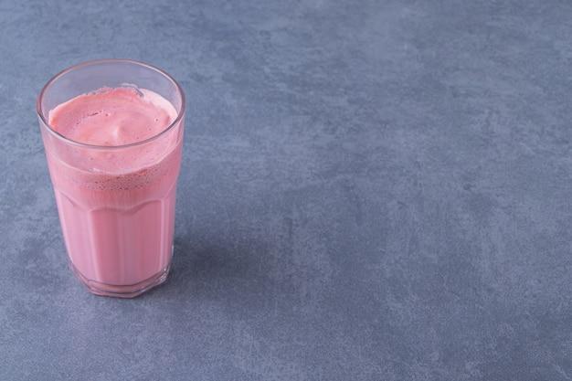 Mocha latte rosa com leite em um copo, na mesa de mármore