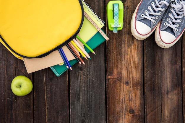 Mochila aberta com artigos de papelaria e sapatos desportivos