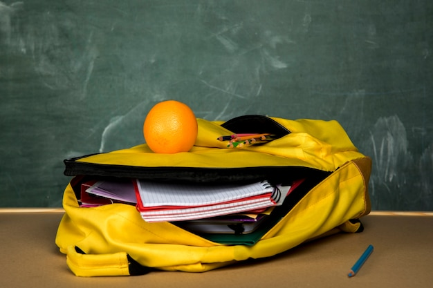 Mochila amarela com cadernos e laranja