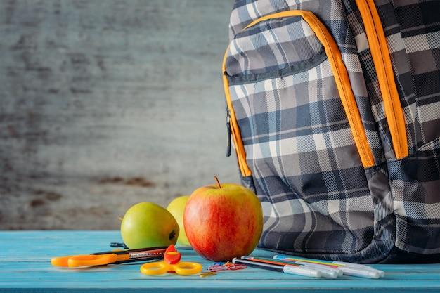 Mochila, apple e material escolar em fundo de madeira