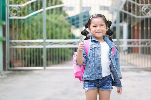 Mochila asiática do ombro e do estudante da menina com divertimento feliz e mostra o dedo do polegar para sempre,
