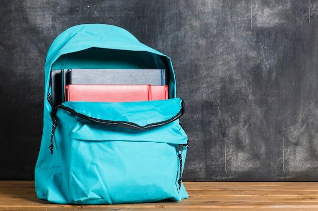 Mochila azul com livros didáticos