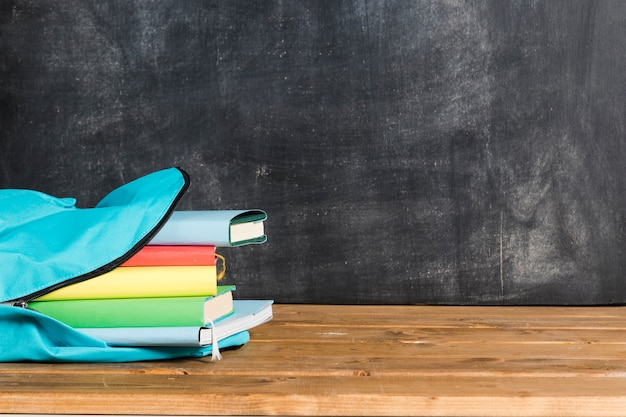 Mochila azul com livros na mesa de madeira