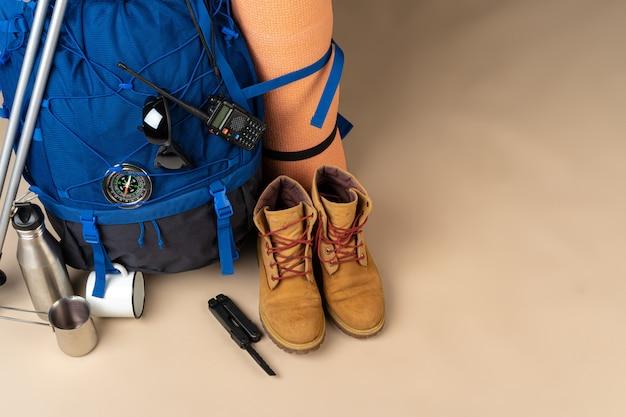 Mochila azul e botas de caminhada. engrenagem de montanha close-up