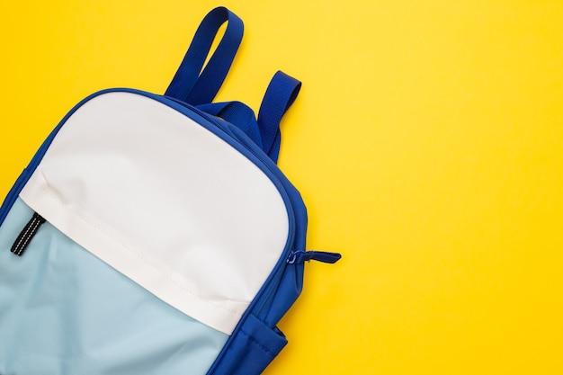 Mochila azul e branca em fundo amarelo