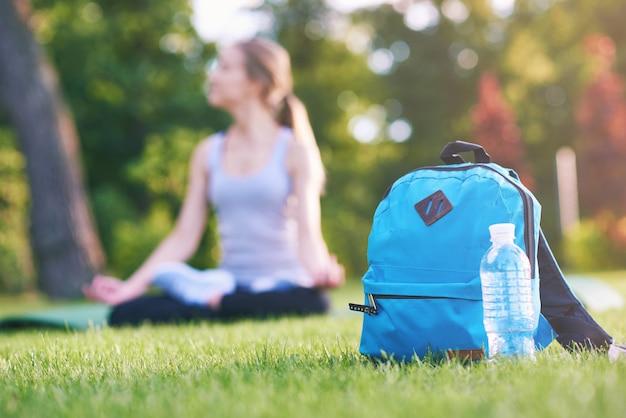 Mochila azul e uma garrafa de água no parque na grama copyspace