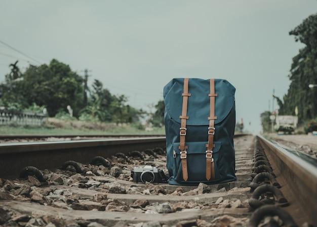Mochila, câmera, colocada nos trilhos para os viajantes. estilo vintage.