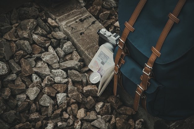 Mochila, câmera, passaporte, bússola, colocada nos trilhos para os viajantes. estilo vintage.