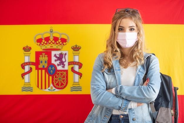 Mochila caryying aluna em frente à bandeira espanhola com uma máscara facial.