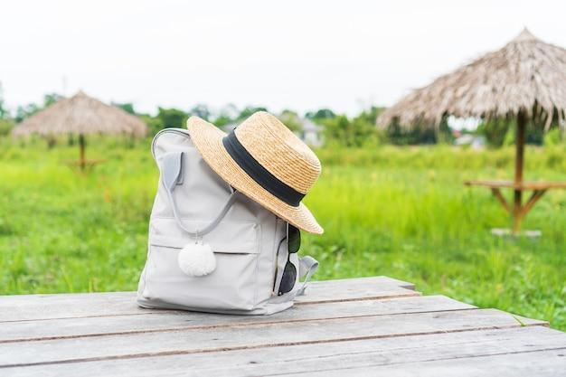 Mochila com chapéu de palha e óculos de sol no campo conceito de viagens