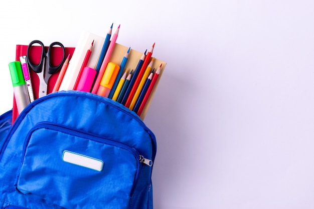 Mochila com diferentes artigos de papelaria coloridos na mesa branca. volta ao conceito de escola.