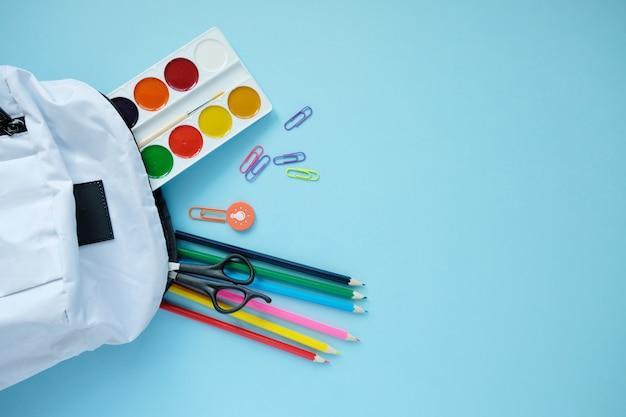 Mochila com diferentes artigos de papelaria coloridos na mesa.