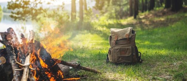 Mochila de caminhada na floresta na margem do rio perto da fogueira