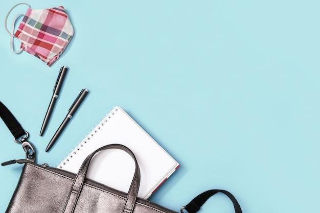 Mochila de couro cinza com material escolar, máscara facial canetas para cadernos