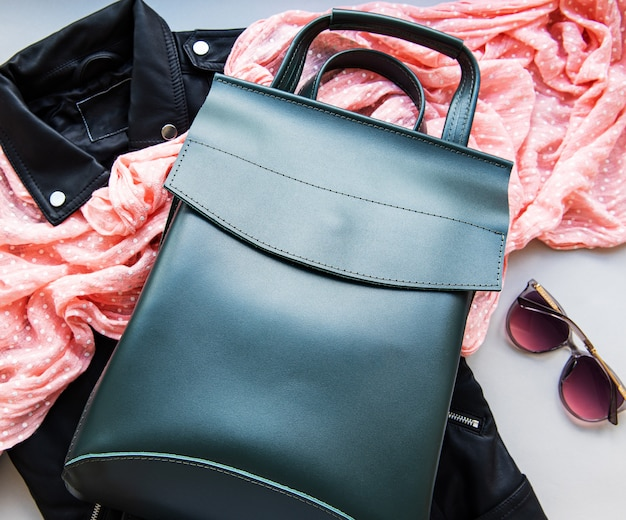 Mochila de couro verde com óculos de sol