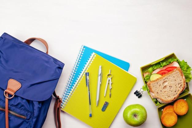 Mochila de estudante, material escolar e sanduíche fresco