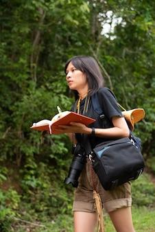 Mochila de jovem adolescente e segurando o livro na mão, andando em um parque