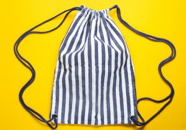 Mochila de praia de tecido listrado na mesa amarela.