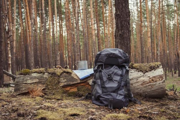 Mochila de turista, caneca de metal e mapa na floresta. conceito de uma caminhada para a floresta ou montanhas