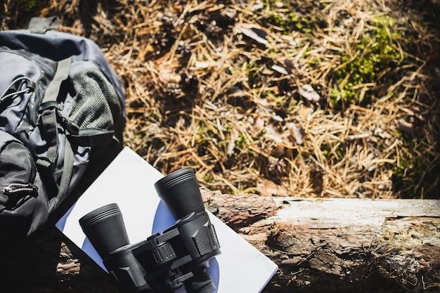 Mochila de turista, chapéu, binóculos e um mapa em um tronco na floresta. conceito de caminhadas, caminhadas nas montanhas. bandeira. vista do topo.
