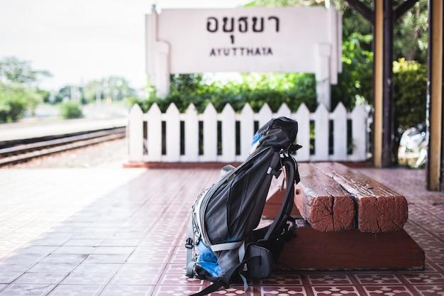 Mochila de viagem trocadilho com cadeira de madeira na estação de trem de ayutthaya