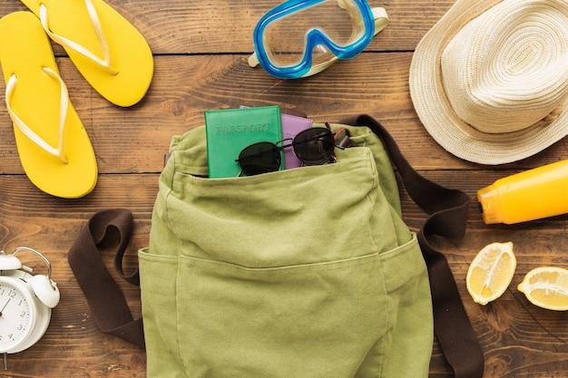 Mochila de viajante de férias de verão com passaportes e itens de férias em madeira