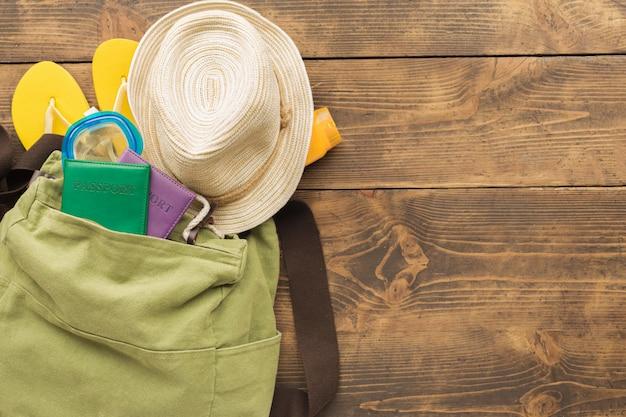 Mochila de viajante de férias de verão com passaportes e itens de férias na mesa de madeira