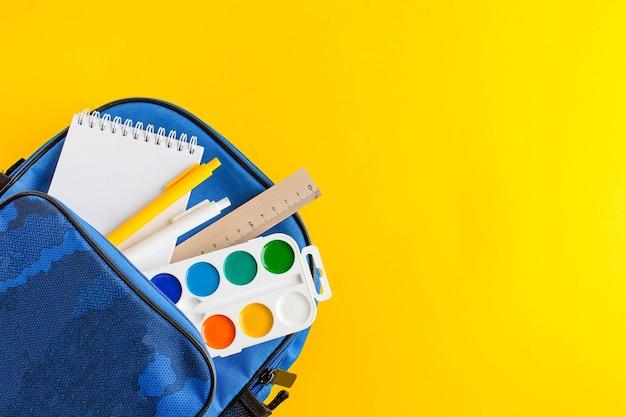 Mochila escolar aberta com bloco de notas, canetas