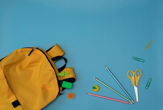 Mochila escolar amarela com escola ou material de escritório sobre fundo azul. de volta à escola estacionário