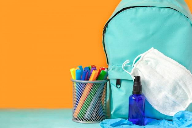 Mochila escolar azul com máscara, desinfetante para as mãos e artigos de papelaria na mesa. nova vida normal.