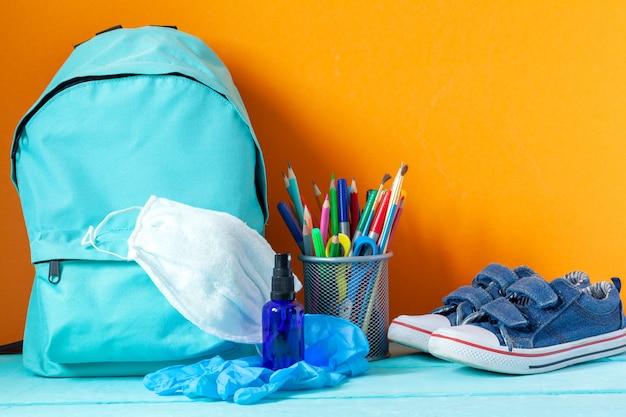 Mochila escolar azul com máscara, desinfetante para as mãos e artigos de papelaria na mesa. novo conceito de vida normal.