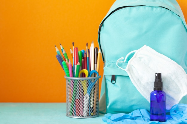 Mochila escolar azul com máscara, desinfetante para as mãos, luvas e artigos de papelaria na mesa. nova vida normal.