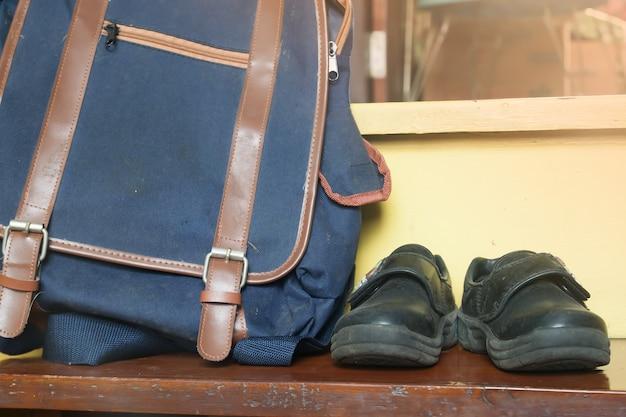 Mochila escolar e sapatos antigos, não está pronto para a escola, conceito de voltar para a escola