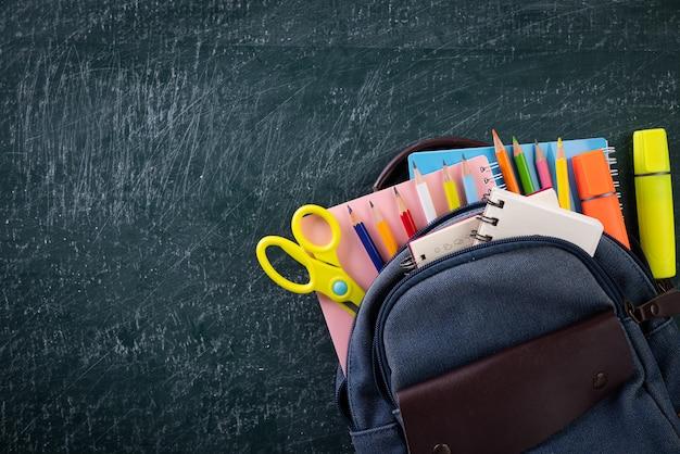 Mochila escolar e suprimentos com lousa. volta ao conceito de escola.