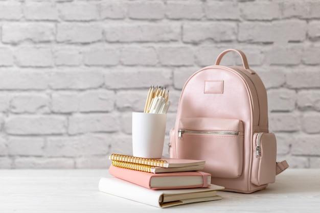 Mochila escolar feminina com material de papelaria na mesa em tijolo branco do sótão. conceito de volta às aulas